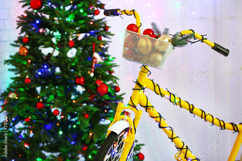 Yellow bicycle near Christmas tree - 74512419