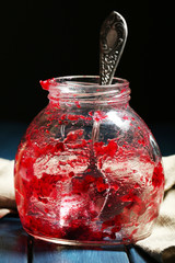 Empty fruity jam jar on table, on dark background