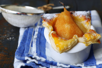 Small pear pie in cup, on wooden table
