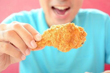 A man with opening mouth about to eat deep fried chicken leg or