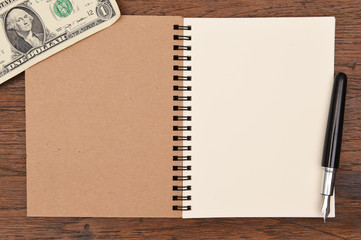 one dollar bill and pen with notebook  for background.