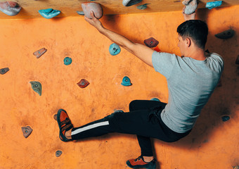 Man climbing up on wall indoors