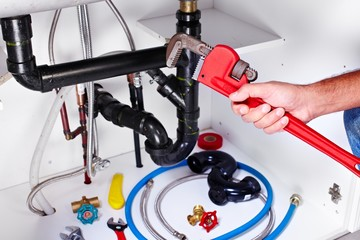 Plumber hands with a wrench.