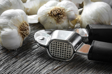 Garlic Press and Garlic Bulb Close Up on Rustic Wood Background