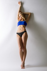 Slim blonde posing leaning against wall