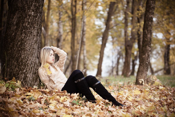 Beautiful elegant woman sitting in a park in autumn