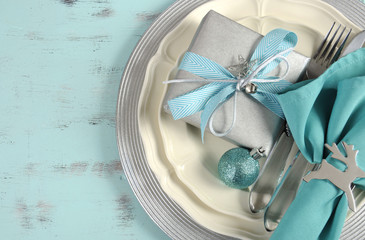 Christmas table place settings in aqua blue, silver and white