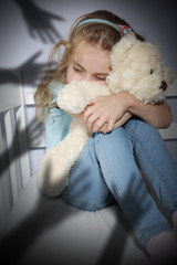 Bullying frightened child hugging a teddy bear