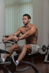 Young Man Doing Back Exercises In The Gym