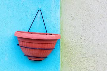 Vaso vuoto appeso su un muro azzurro