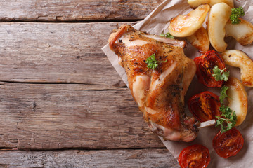 tasty roast leg of rabbit with apples and tomatoes top view