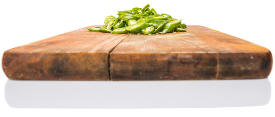 Chopped green chili peppers on wooden cutting board