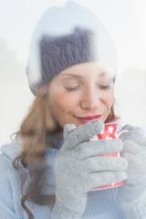 Pretty redhead in warm clothing holding mug