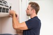 Leinwandbild Motiv Focused handyman testing air conditioning