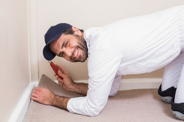 Handyman laying down a carpet