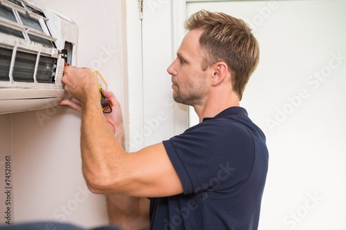 Focused handyman testing air conditioning - 74520861