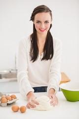 Pretty brunette making dough on counter