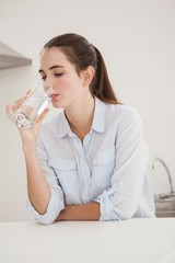 Pretty brunette drinking glass of water