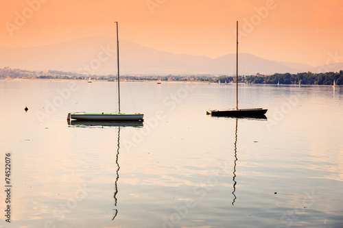 boats on a calm lake surface at sunset - 74522076