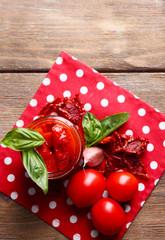 Sun dried tomatoes in glass jar, basil leaves