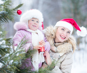 Happy family mother and kid decorating christmas tree outdoor