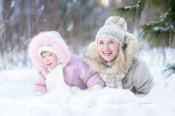 Happy family mother and daughter  playing with snow in winter