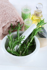 Branches of rosemary, towels and bottle with massage oil