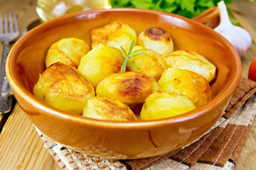Potatoes fried in ceramic pan on napkin