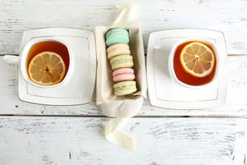Colorful macaroons with cup of tea on color wooden  background