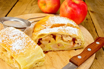 Strudel apple with strainer and knife on board