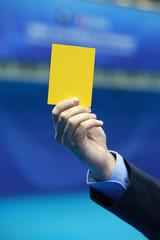 Arbitre brandissant un carton jaune