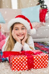 Festive little girl smiling at camera with gift