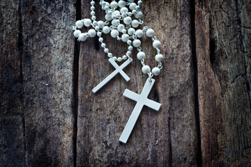 necklace white crucifix on old wooden table