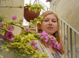 Portrait of a pretty red-haired woman behind pink flowers
