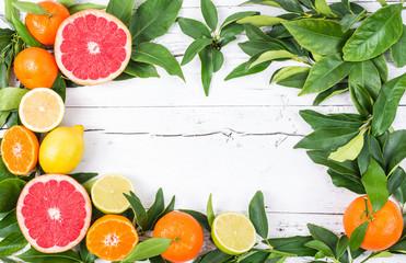Citrus fruits frame on white wood background.