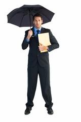 Businessman standing under umbrella while holding folder