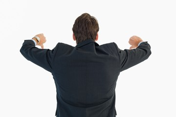 Rear view of businessman gesturing thumbs down