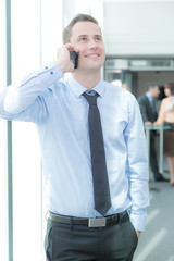Junger Geschäftsmann mit Telefon