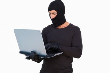 Burglar with leather gloves using laptop