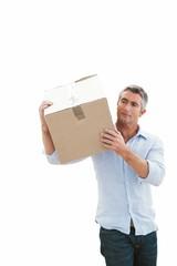 Cheerful man carrying cardboard box