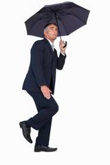 Businessman in suit standing under umbrella