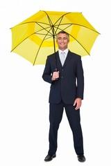 Smiling businessman under yellow umbrella