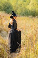 woman in witch's hat standing back, looking to camera