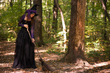 woman in witch's hat holding broom and looking downwards