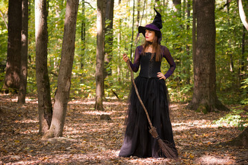 woman in witch's hat holding broom