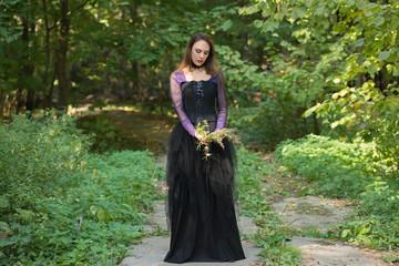 woman in floor-length dress holding wild flowers