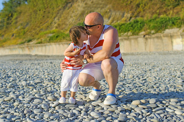 Father kissing his 2 years son in similar clothes on the seaside