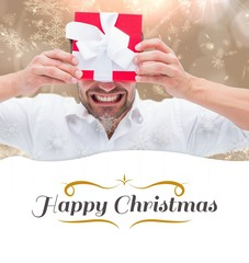 Composite image of festive man holding christmas gift