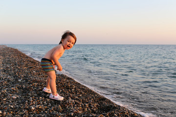 Happy smiling 2 years boy standing on the pebbles beach at sunse