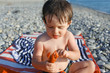 little boy with crawfish on the seaside